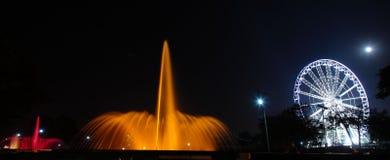 Rueda y fuente iluminadas en la noche Foto de archivo