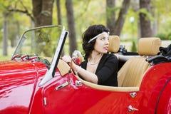 Rueda y mirada de coche del asimiento de la mujer detrás Imagen de archivo