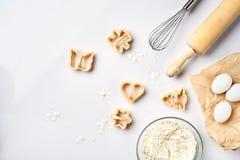 Ruedan con la harina de trigo, rodillo, baten, los huevos, cortadores de la galleta Opinión superior sobre una tabla blanca con u Fotos de archivo libres de regalías