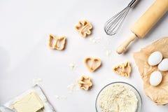 Ruedan con la harina de trigo, rodillo, baten, los huevos, cortadores de la galleta Opinión superior sobre una tabla blanca con u Foto de archivo