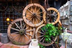 Ruedas antiguas del carro, pared adornada con las ruedas, ShopWall antiguo fotografía de archivo