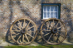 Ruedas de carro rústicas delante de una pared bricked imagen de archivo libre de regalías