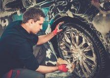 Ruedas de la aleación del coche que se lava del trabajador del hombre foto de archivo libre de regalías