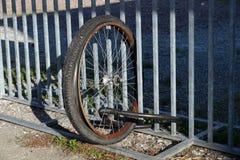 Ruedas desmontadas sin la bici atada a una puerta de la ciudad Fotografía de archivo