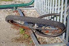Ruedas desmontadas sin la bici atada a una puerta de la ciudad Fotos de archivo