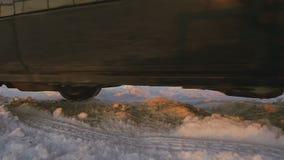 Ruedas grandes del coche moderno en el camino del invierno metrajes