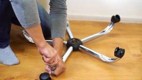 Ruedas o echadores de junta del hombre con la base de la silla de la oficina en casa metrajes