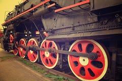 Ruedas rojas del tren del vapor en los carriles Fotos de archivo libres de regalías
