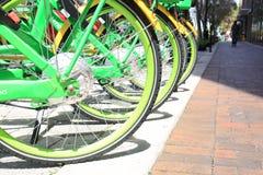 Ruedas verdes y amarillas de la bici en una calle de la ciudad foto de archivo