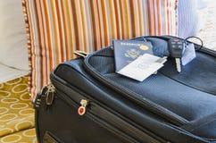 Ruede a bordo de bolso en una cama del hotel Foto de archivo libre de regalías