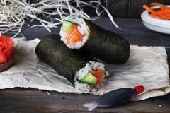 Ruede con el estilo de color salmón del nori, fondo negro, aún vida, cierre para arriba, los alimentos de preparación rápida Imagen de archivo libre de regalías