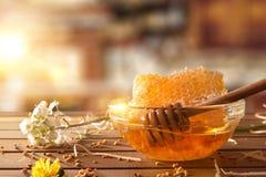 Ruede con el panal y el cazo de la miel en cocina rústica Fotografía de archivo libre de regalías