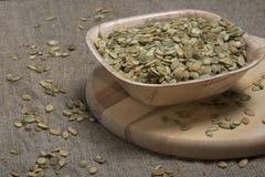Ruede con las semillas de calabaza en la tabla de cortar redonda Foto de archivo
