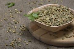 Ruede con las semillas y la albahaca de calabaza en la tabla de cortar redonda Foto de archivo