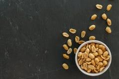 Ruede con los cacahuetes asados y salados en una pizarra con el espacio de la copia Foto de archivo libre de regalías