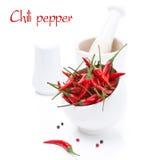 Ruede con pimienta y el mortero de chiles rojos caliente fresca, aislados Foto de archivo