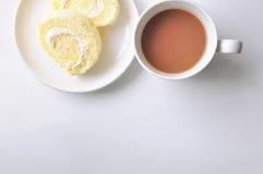 Ruede la torta en la placa blanca y una taza de cacao Foto de archivo libre de regalías