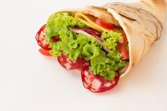 Ruede la tortilla con las hierbas, el queso y la carne en el fondo blanco Imágenes de archivo libres de regalías