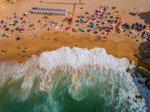 Ruede las ondas delanteras en la playa con los turistas fotos de archivo