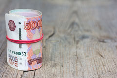 Ruede los billetes de banco rusos en el viejo tablero de madera gris con las grietas Imagenes de archivo