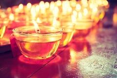 Ruegue el vidrio de la vela en la tabla de madera en templo chino foto de archivo