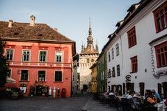 Rues de la ville médiévale Sighisoara, Roumanie de soirée Bâtiments et cafés antiques de rue image stock