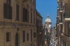 Rues et bâtiments à La Valette du centre, Malte, avec le dôme de la basilique de notre Madame du mont Carmel photos libres de droits