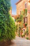 Rues médiévales tordues avec les fleurs colorées en Toscane Photo libre de droits