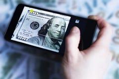 Rufen Sie in der Hand, Bild des Dollars, auf dem Hintergrund von Dollar an Stockfoto
