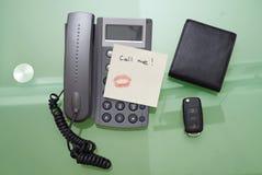 Rufen Sie mich geschrieben auf eine Karte mit Kuss mit Lippenstift auf dem Phon an Stockfotografie