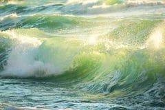 Ruffa mot den kulöra havvågen som ner bryter, soluppgångskottet Royaltyfri Foto