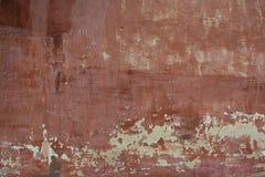 Ruffa mot den texturerade röda gamla cementväggen för bakgrund med Royaltyfri Bild