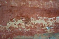 Ruffa mot den texturerade röda gamla cementväggen för bakgrund med Arkivbilder