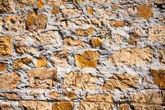 Ruffa mot den texturerade väggen som göras av tegelstenar, stenar, betong Royaltyfria Foton