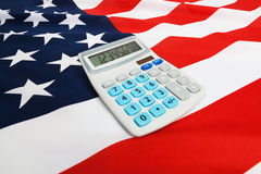 Ruffled national flag with calculator over it - United States Stock Images