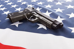 Ruffled national flag with hand gun over it series - USA Stock Images