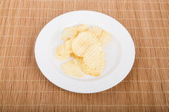 Ruffled Potato Chips on White Plate and Bamboo Mat Stock Photography