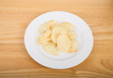 Ruffled Potato Chips on White Plate and Wood Table Royalty Free Stock Photos