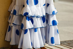 Ruffles on blue white poka dot flamenco dress. Ruffles and flounces at hemline of white Spanish flamenco dancer dress with blue pokadots hanging outside store in Royalty Free Stock Photography