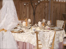 Ruffles and Roses. An ornately decorated wedding table with assorted china pieces atop rose-petaled, textured satin cloth.  Background is a cedar wall.  Billowy Royalty Free Stock Photo