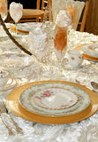Ruffles and Rosettes. An ornately decorated wedding table with assorted china pieces atop rose-petaled, textured satin cloth Royalty Free Stock Photos