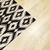 Rug with ethnic design on wooden floor Stock Photography