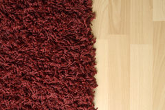 Rug on floor. Red fluffy rug on laminate floor Royalty Free Stock Images