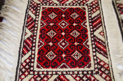 Rug handmade with black pattern on red background Royalty Free Stock Images