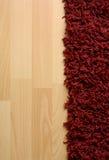 Rug on laminate floor. Red fluffy rug on laminate floor Stock Image