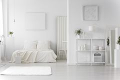 Minimal white bedroom interior. Rug in minimal white bedroom interior with empty poster above bed next to chair Stock Images