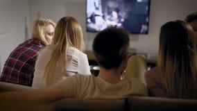 Rug van gelukkige groep van vijf vrienden wordt geschoten die op bank in woonkamer zitten en op een film op TV letten, weekends d stock video