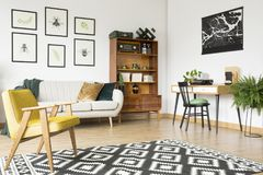 Rug in vintage flat interior. Geometrically patterned rug lying on a wooden floor of a vintage flat interior with beige sofa and cabinet royalty free stock photo