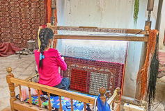 In the rug workshop. BUKHARA, UZBEKISTAN - APRIL 28, 2015: The young woman weave the traditional Uzbek rug at the workshop, on April 28 in Bukhara Stock Image