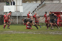 Rugby action on muddy field Stock Photography